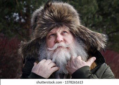 Closeup face portrait of wistful elderly stylish hipster with splendid mustache and beard. Senior caucasian man wearing a fur cap with tabs over the ears and brushing beard by hands.