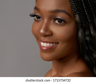 Closeup face portrait of young african woman with makeup and long black hair with african pigtails posing over gray backgound.