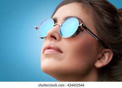Close-up face portrait of young beautiful woman with perfect skin in round sunglasses looking up on the blue background. Beauty make-up.
