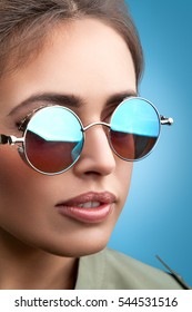 Close-up face portrait of young beautiful woman with perfect skin in round sunglasses looking up on blue background. Beauty face make-up.