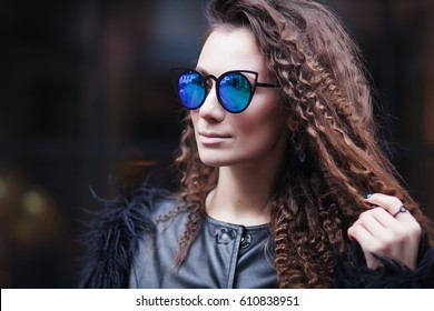 Close-up face portrait of young beautiful woman with perfect skin in Cat's eye sunglasses in the cityscape. Beauty face make-up