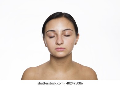Close-up face portrait of young woman with my eyes closed without make-up against white background