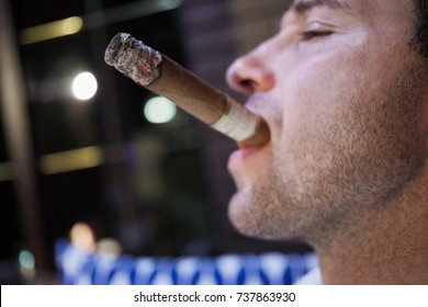 Closeup face in profile of man with burning cigar in mouth.