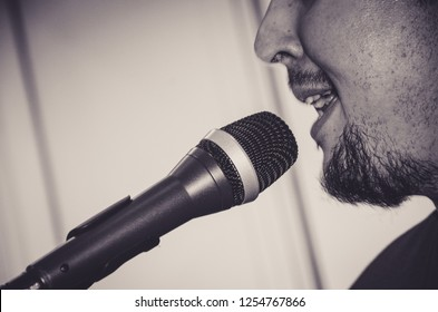 Close-up face of the singer with microphone and singing on black and white background , musical concept