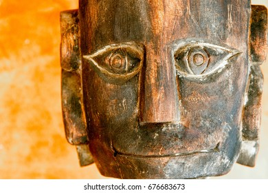 Closeup of the face a tribal style wooden statue.