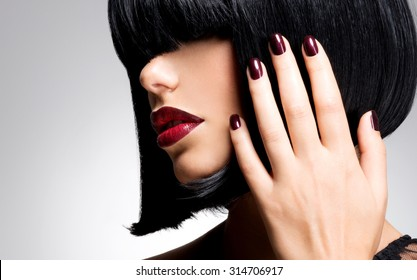 Closeup face of a woman with beautiful sexy red lips and dark nails - studio