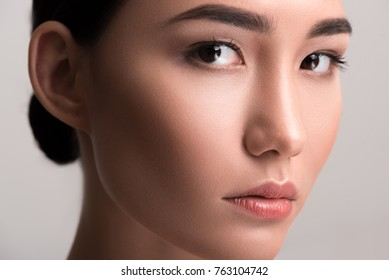 Close-up of face of young asian woman with perfect and soft skin. She is looking at camera dreamily. Isolated background