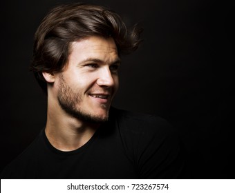 Close-up face of young bearded man on dark background modern and dramatic photo