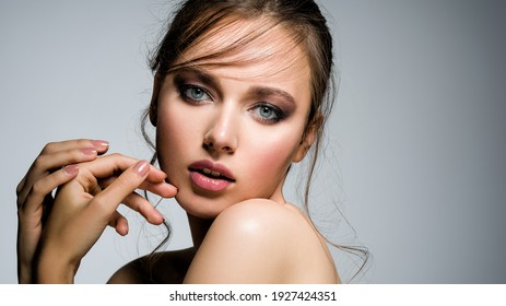 Closeup face of young beautiful woman with a healthy clean skin.  Pretty woman with bright  makeup of eyes. Beautiful white girl. Portrait of a beautiful girl with a long curl of hair hanging down.