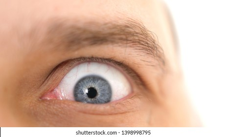 Close-up face of a young emotional shocked man with blue eye