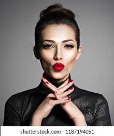 Closeup face of an young excited woman. Caucacian young adutl girl with a kiss gesture. Gorgeous female with red lipstick ona lips.