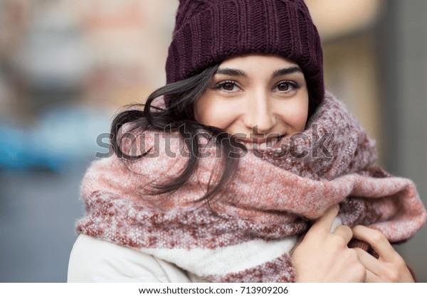 スカーフと帽子をかぶった冬を楽しむ若い幸せな女性の接写。カラフルなショールを着た笑顔の女の子がカメラを見ている。ニットボルドー帽とウールンスカーフを持つラテン女性。