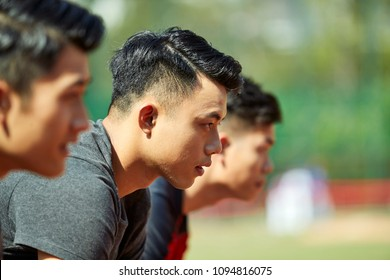 close-up of faces of young asian adult runners on starting line.