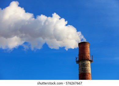 close-up factory brick chimney. The smoke from the brick chimney cogeneration plant. Steam escaping from a pipe on the sky background in the sunlight. Ambient air pollution industrial emissions