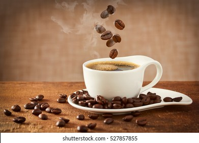Closeup of falling coffee beans in cup on dark background