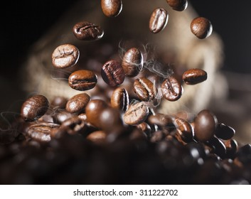 Closeup of falling coffee beans with focus on one