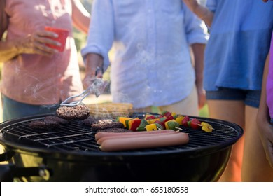 Close-up of family grilling patties, vegetables and sausages on the barbecue grill