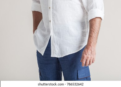 Closeup fashion image of business man holding one hand in linen trousers. Man holds his hans in blue jeans pocket. Man in casual outfit standing and holding his hand in a pocket.