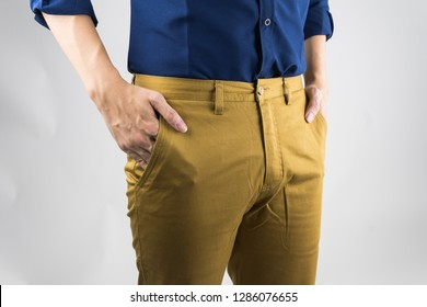 closeup fashion image business man.body detail of a business man.Man's hand in a navy shirt brown chino pants pocket closeup. fashion men business concept, on white background.