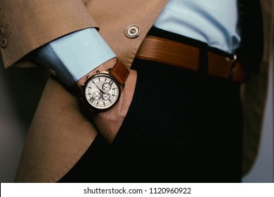 Closeup fashion image of luxury brown  watch on wrist of man.body detail of a business man.Man's hand in pants pocket closeup at white background.Man wearing beige jacket and white shirt.Not isolated