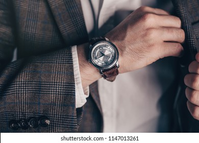 closeup fashion image of luxury watch on wrist of man.body detail of a business man.Man's hand in a checkered with cufflinks in jacket pocket closeup. Tonal correction