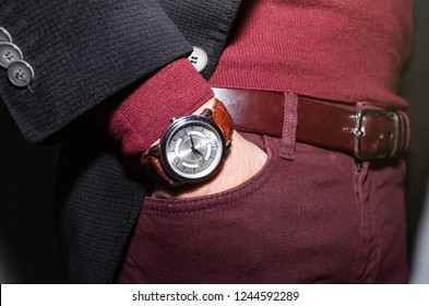 Closeup fashion image of luxury watch on wrist of man.body detail of a business man.Man's hand in brown pants pocket closeup at white background.Man wearing black jacket and bordo sweater.