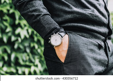 closeup fashion image of luxury watch on wrist of man.body detail of a business man.Man's hand in a grey shirt with cufflinks in a pants pocket closeup. Tonal correction