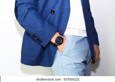Closeup fashion image of luxury watch on wrist of man.body detail of a business man.Man's hand in blue pants pocket closeup at white background.Man wearing blue jacket and white t shirt.Not isolated