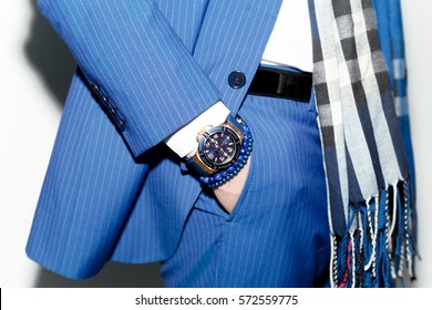 Closeup fashion image of luxury watch on wrist of man.body detail of a business man.Man's hand in blue pants pocket closeup at white background.Man wearing blue jacket and white shirt.Not isolated