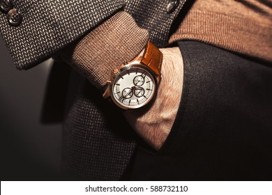 Closeup fashion image of luxury watch on wrist of man.body detail of a business man.Man's hand in brown pants pocket closeup at white background.Man wearing brown jacket and beige sweater.