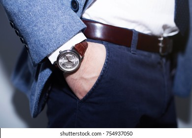 Closeup fashion image of luxury watch on wrist of man.body detail of a business man.Man's hand in wool blue jacket,in dark blue pants pocket closeup.Casual outfit. Tonal in a business suit close up