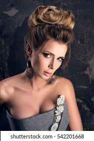 Closeup fashion portrait of beautiful young woman in evening dress. Complicated hairstyle, professional makeup and sensual look. Dark gray wall in the background