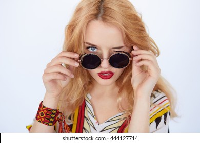 Closeup fashion portrait of blonde young hippie woman in boho style clothes and sunglasses with red lips winking to camera on white background