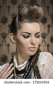 close-up fashion portrait of charming female with creative look, cute brunette hair-style and strong make-up. Wearing white lace shirt and a lot of necklaces