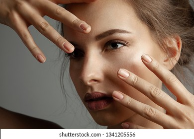 Close-up fashion portrait of girl with perfectly clean skin. Pretty model looking away and showing nice manicure. Beauty and lifestyle concept. Blurred grey background