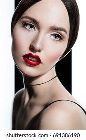 Closeup fashion portrait of model with bright red lips, on black and white background