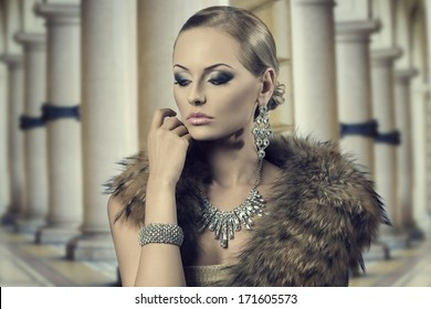 close-up fashion portrait of sensual blonde girl with luxury style, posing with elegant hair-style and make-up and wearing fur shawl and rich shiny jewellery. Aristocratic expression