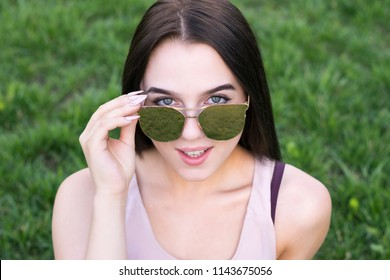 Close-up fashion portrait of sensual young female with big beautiful blue eyes. Stunning model with natural makeup sitting on green grass. Blurred background