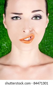 Closeup fashion portrait of a woman pulling a strange face isolated on green