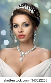 Closeup fashion portrait of young beautiful rich woman in dress with decollete and jewelry. Pretty girl wearing diadem, earrings and necklace. Bokeh background
