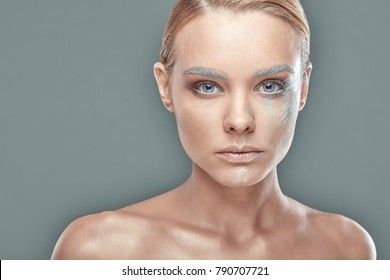 Close-up fashion portrait of young blonde woman with light blue eyes and blue silver artistic make-up. Studio shot