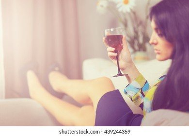 Closeup fashion portrait of young sexy hot woman sitting relaxed on comfortable luxury sofa and drinking wine