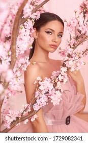 Closeup fashion spring face portrait of young beautiful caucasian woman with brunette hair in pony tail and perfect makeup looking through trees with pink flowers in blossom