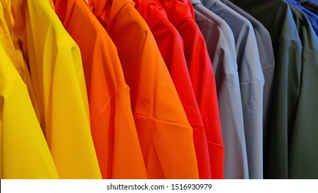 Closeup of fashion waterproof colorful raincoat (yellow, orange, red, grey, blue, green color) hanging on hanger at clothes shop in the shopping mall. Colorful water-resistant rain jacket concept.