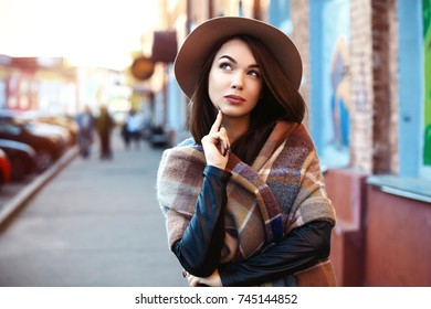Close-up Fashion woman portrait of young pretty trendy girl posing at the city, autumn street fashion,holding retro fedora hat. laughing and smiling portrait.trendy
