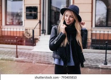 Close-up Fashion woman portrait of young pretty trendy girl posing at the city in Europe,spring street fashion,wearing leather jacket,wide hat, scarf and sweater, laughing and smiling portrait.trendy