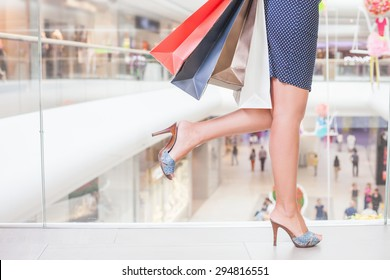 Closeup fashion woman's legs runs or rush for shopping discounts and sales at the big mall center. Concept of shopping or shopaholic, sale and discounts at boutique