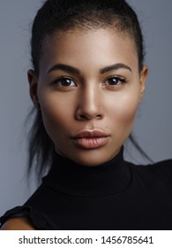 Closeup fashionable portrait of a beautiful metis young woman with perfect smooth glowing skin, full lips and collected hair. Studio shoot of an african american female model with nude fresh makeup