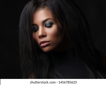 Closeup fashionable portrait of a beautiful young woman with close eyes, full lips and black lush loose hair. Studio shoot of an african american female model with the bright makeup on her face