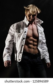 Closeup of fashionable young man with open shirt showing ripped abdominal muscles.